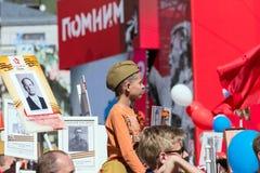 日莫斯科胜利 一个军用试验` s盖帽的一个男孩坐他的父亲` s肩膀 库存图片