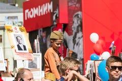 日莫斯科胜利 一个军用试验` s盖帽的一个男孩坐他的父亲` s肩膀 免版税库存图片