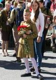 日莫斯科胜利 军服的美丽的女孩有红色花的在胜利天 免版税库存照片