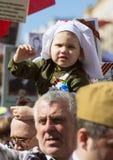 日莫斯科胜利 医疗制服的美丽的女孩有红色花的在胜利天 免版税图库摄影