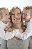 日获得愉快的拥抱亲吻妈妈母亲 免版税库存图片