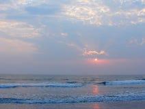 日落、云彩和反射在海水的Payyambalam靠岸, Kannur,喀拉拉,印度 免版税库存照片