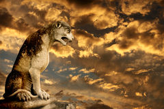 日落、古老狮子雕象和风暴天空 免版税库存照片