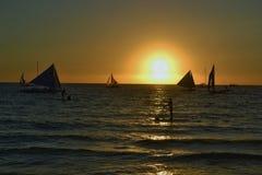 日落、风船和风平浪静在博拉凯海岛,菲律宾 免版税库存图片