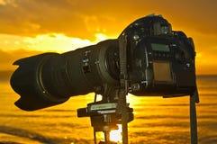 日落一台照相机的海滨视图在三脚架的 库存照片