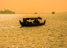 日落一条小船的剪影场面从喀拉拉的死水的 库存照片