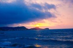 日落从海岸线的海透视,美好的山和海景环境美化,与蓝色和黑暗的col的闪烁微明 免版税图库摄影