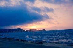 日落从海岸线的海透视,美好的山和海景环境美化,与蓝色和黑暗的col的闪烁微明 免版税库存照片