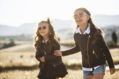日落光的两个岩石女孩 免版税库存图片
