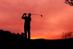 日落准备的高尔夫球运动员 库存照片