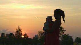 日落剪影:年轻母亲抱她的城市公园身分的男婴孩子在落日前面和生动 股票录像