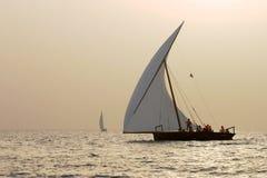 日落单桅三角帆船 库存图片