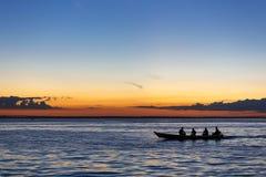 日落和剪影在巡航的小船亚马孙河,巴西 库存照片