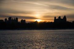 日落和剪影大厦在湖 免版税库存照片