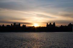 日落和城市在湖反射在曼哈顿 免版税库存图片