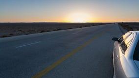 日落和沙漠高速公路路15在约旦 免版税图库摄影