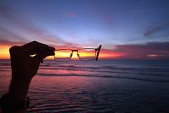 日落和海洋通过玻璃在手上 图库摄影