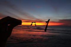 日落和海洋通过玻璃 库存图片