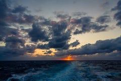 日落和漂移在加勒比海的热带水的剧烈的套云彩在白天之前的最后片刻点燃 库存图片