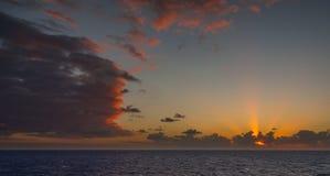 日落和漂移在加勒比海的热带水的剧烈的套云彩在白天之前的最后片刻点燃 免版税库存照片