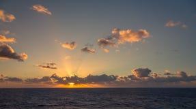 日落和漂移在加勒比海的热带水的剧烈的套云彩在白天之前的最后片刻点燃 图库摄影