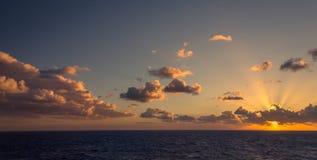 日落和漂移在加勒比海的热带水的剧烈的套云彩在白天之前的最后片刻点燃 免版税库存图片