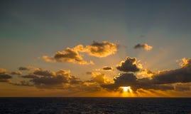 日落和漂移在加勒比海的热带水的剧烈的套云彩在白天之前的最后片刻点燃 免版税图库摄影