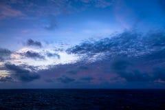 日落和漂移在加勒比海的热带水的剧烈的套云彩在白天之前的最后片刻点燃 库存照片