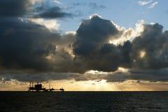 日落和石油平台 免版税库存图片