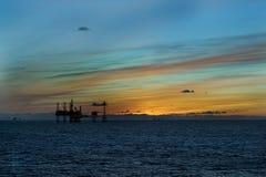 日落和石油平台 免版税库存照片