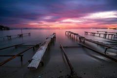 日落和老生锈的码头的颜色 库存照片