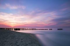 日落和防堤在波罗的海 库存照片