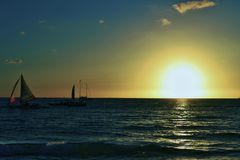 日落和风船在有蓝色和橙色天空的博拉凯海岛 免版税图库摄影