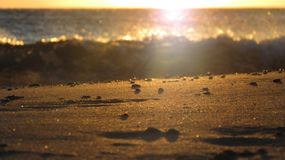日落在一个海滩的希腊与在前景的沙子 免版税图库摄影