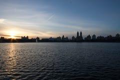 日落在与天空蔚蓝的湖和剪影大厦反射 免版税库存照片
