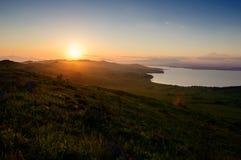 日落在小山和海 免版税库存照片