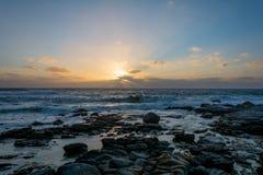 日落在开普敦,有飞溅的南非挥动 免版税库存照片