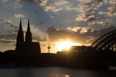 日落在有大教堂和桥梁的科隆 免版税库存图片