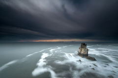 日落在有岩石的海 免版税图库摄影