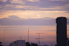 日落在有甜紫色桃红色天空的一个城市 库存照片