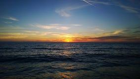 日落在海温暖的秋天晚上-太阳的色的光芒,在水,有些云彩的反射期间 免版税库存照片