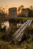 日落在被毁坏的桥梁附近的乡下 免版税库存图片