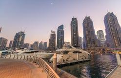 日落在迪拜小游艇船坞 在人为加州的大厦反射 库存图片