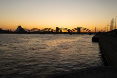 日落在里加有在流浪者道加瓦河的一个看法和中央桥梁- 2019年 免版税库存照片