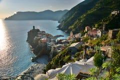 日落在韦尔纳扎 Cinque Terre,利古里亚, Cinque Terre,即Riomaggiore五个村庄的Italy.Crowded轮渡运载的游人, Manarola、Corniglia、Vernazza和Monterosso.Picture可以被用 免版税图库摄影