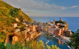 日落在韦尔纳扎 Cinque Terre,利古里亚, Cinque Terre,即Riomaggiore五个村庄的Italy.Crowded轮渡运载的游人, Manarola、Corniglia、Vernazza和Monterosso.Picture可以被用 库存照片