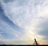 日落地平线的骑自行车者 免版税库存照片