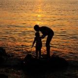 日落墙纸:母亲和儿童储蓄图片 免版税库存照片