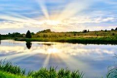 日落夏天风景由河的有反射的 免版税库存照片