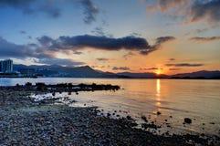 日落多岩石的海滩 库存图片
